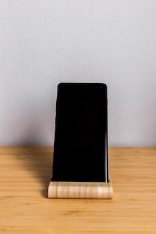 木製の机の上の黒いスマートフォンのクローズアップ