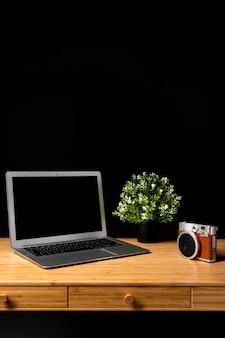 ノートパソコンとカメラ付きの木製デスク
