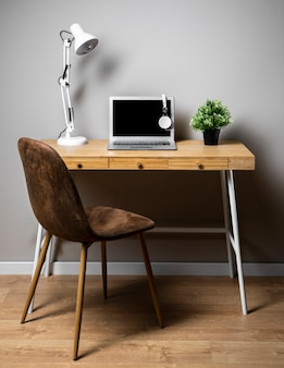 Стол с серым ноутбуком и лампой