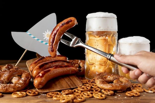 Крупный план гриль вилка с вкусной колбасой и пивом