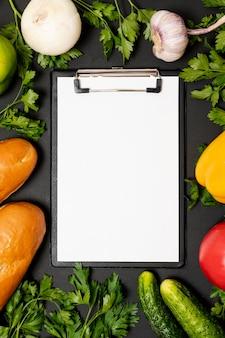 Макет буфера обмена в окружении свежих овощей