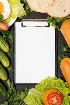 野菜に囲まれたクリップボードのモックアップ