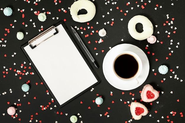 一杯のコーヒーとメレンゲクッキーの配置とモックアップクリップボード