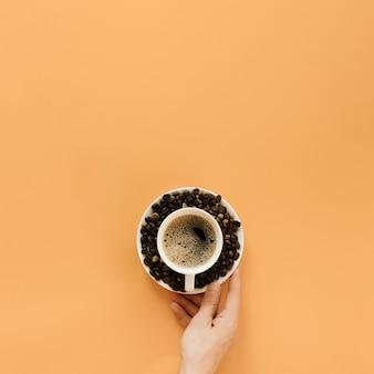 一杯のコーヒーとプレートを持っている手