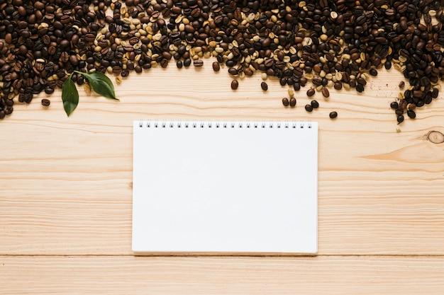 ノートブックモックアップとコーヒー豆のトップビュー