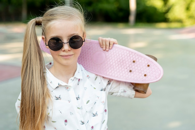サングラスとピンクのスケートボードを持つ少女