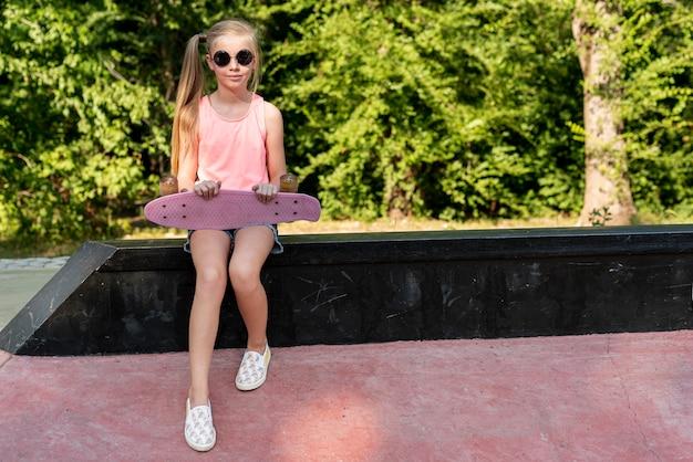 ピンクのスケートボードとサングラスを持つ少女