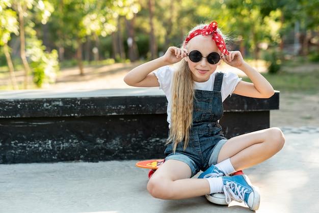 スケートボードの上に座って赤いカチューシャを持つ少女