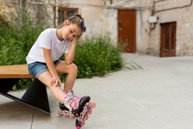 インラインスケートを持つ少女のロングショット