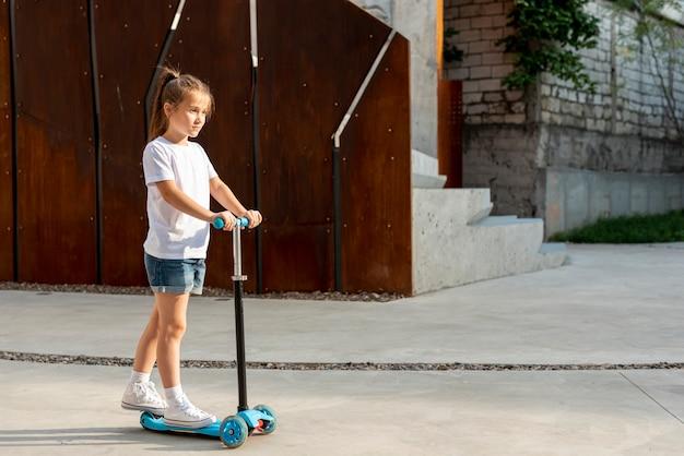 青いスクーターに乗っている女の子の側面図