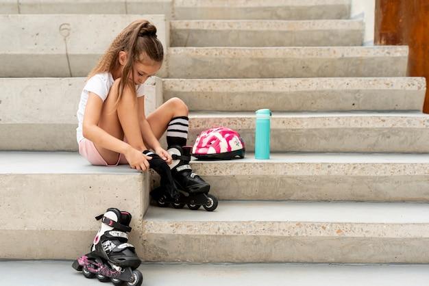 ローラーブレードを置く少女の側面図