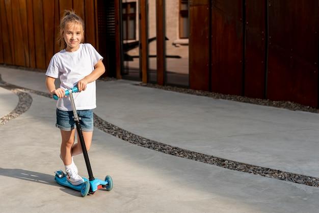 青いスクーターに乗っている女の子のロングショット