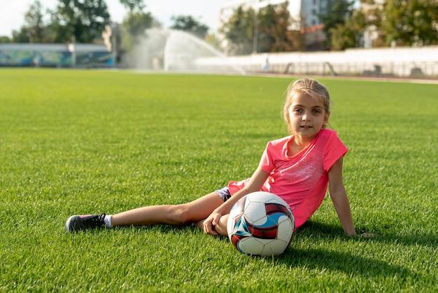 草の上に座っているピンクのシャツの女の子