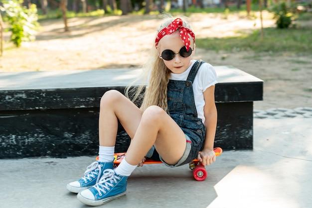 Девушка в темных очках сидит на скейтборде