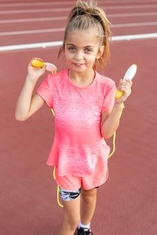 Вид спереди маленькая девочка с прыжки через скакалку