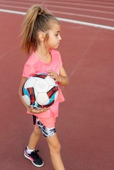 Девушка в розовой футболке держит мяч