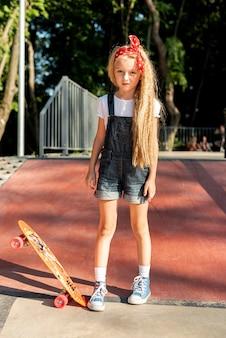 スケートボードを持つ少女のフルショット