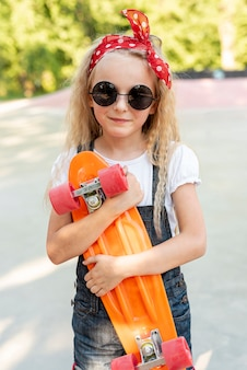 スケートボードを持つ少女の正面図