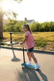 Вид сбоку девушки на синем скутере