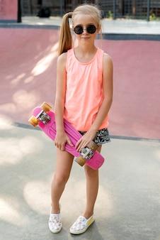 ショートパンツとピンクのスケートボードを持つ少女