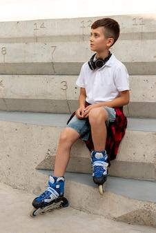 ローラーブレードを持つ少年のフルショット