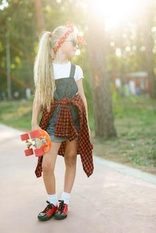 Полный снимок девушки со скейтбордом