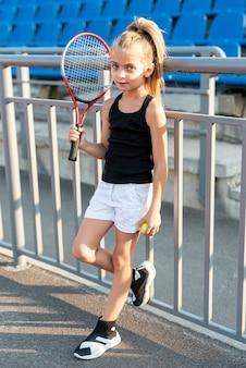 Полный снимок девушки с теннисной ракеткой и мячом