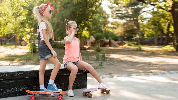 スケートボードを持つ女の子の側面図