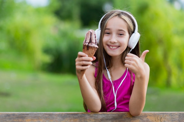 Девушка держит мороженое, давая пальцы