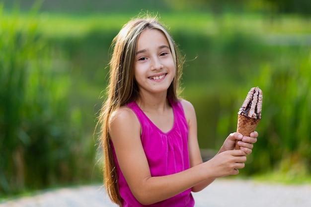 チョコレートとシロップのアイスクリームを保持している女の子