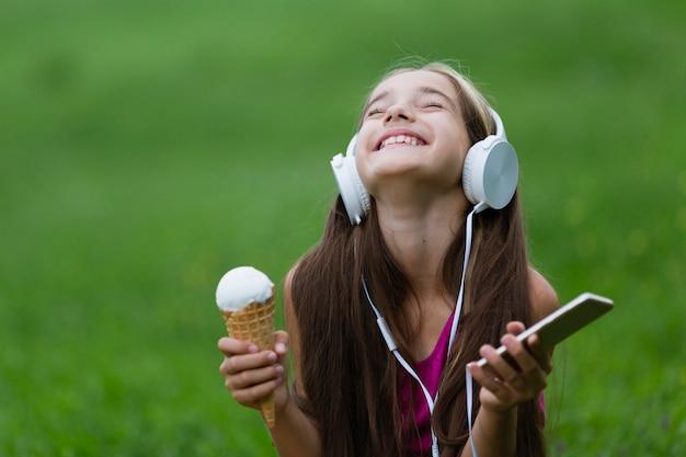 Девушка держит ванильное мороженое и телефон