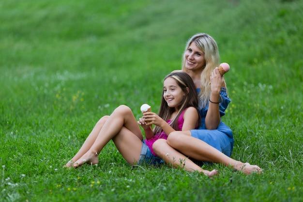 Мать и дочь лежат в траве с мороженым
