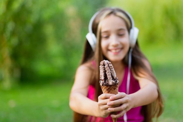 公園でアイスクリームコーンを保持している女の子