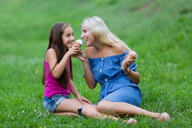 Мама и дочка в парке едят мороженое