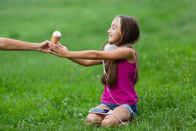 バニラアイスクリームを持つ少女の側面図
