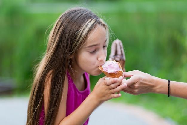 アイスクリームを食べる少女の側面図