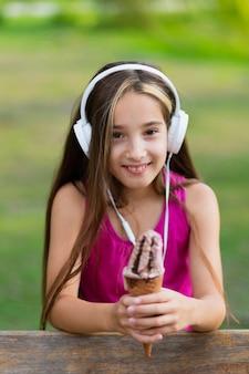 チョコレートアイスクリームコーンを持って笑顔の女の子