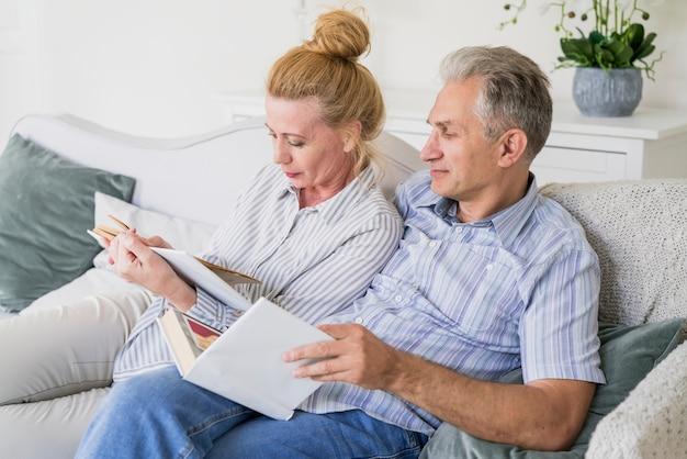 ソファで本を読んで年配のカップル