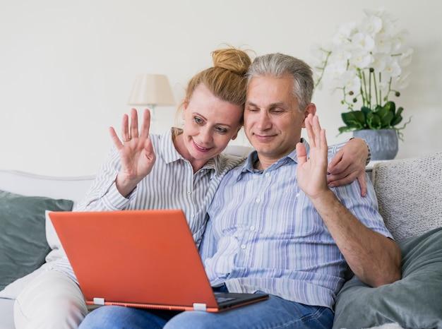 ノートパソコンで手を振っているかわいい年配のカップル