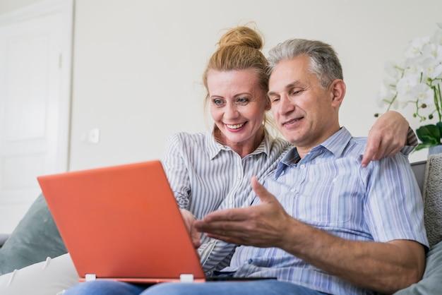 Макро милая пожилая пара с ноутбуком