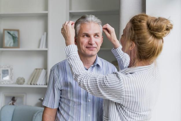 Вид спереди женщина укладывает волосы мужа