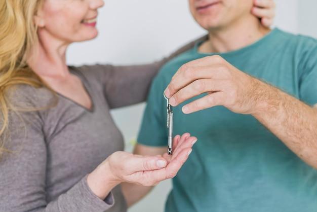 Пожилые супружеские пары руки с ключом крупным планом