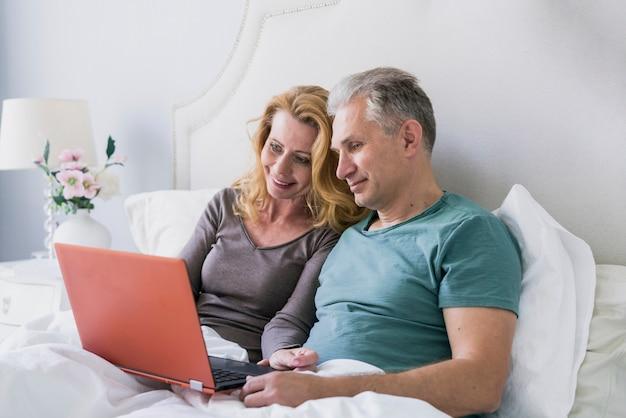 年配の男性と女性が一緒にベッドで