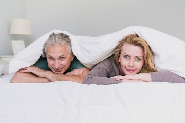 カメラ目線のベッドで正面の年配のカップル