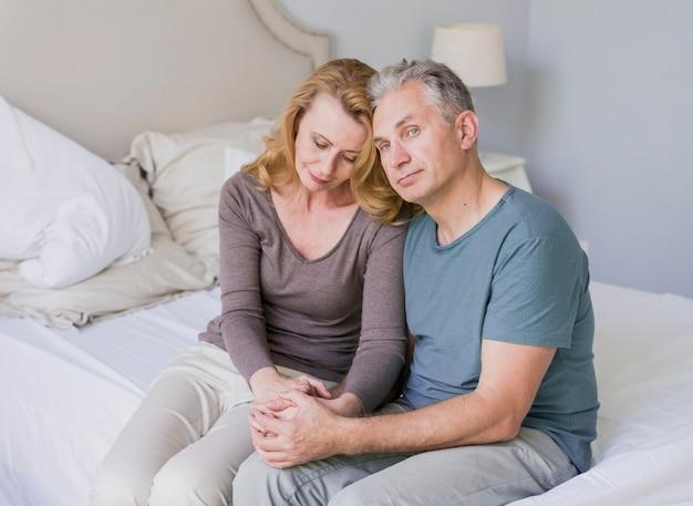 かわいい年配の男性と女性がベッドの上に座って