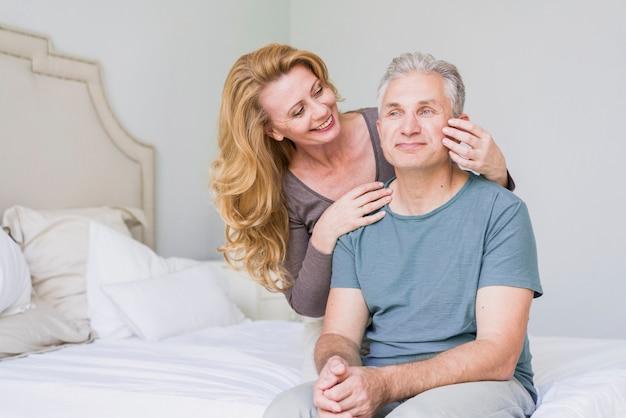 ベッドの中で男に触れるかわいい年配の女性