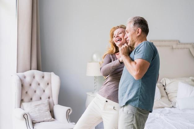 Старший мужчина и женщина смеются вместе