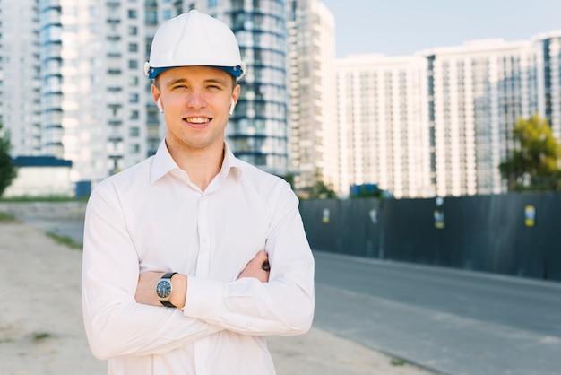 Вид спереди счастливый человек со шлемом и скрещенными руками