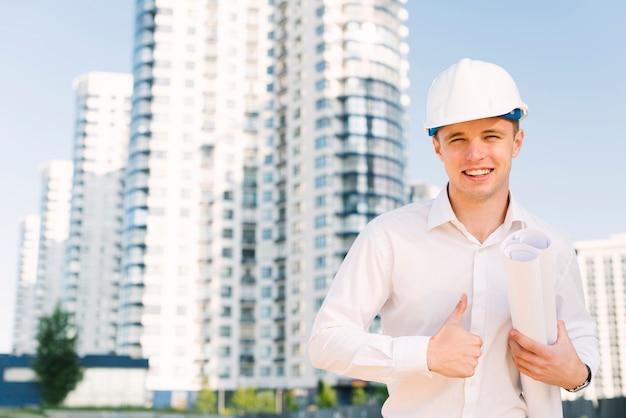 Вид спереди счастливый человек в шлеме, показывая одобрение