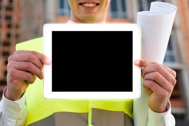 Крупным планом смайлик человек держит планшет